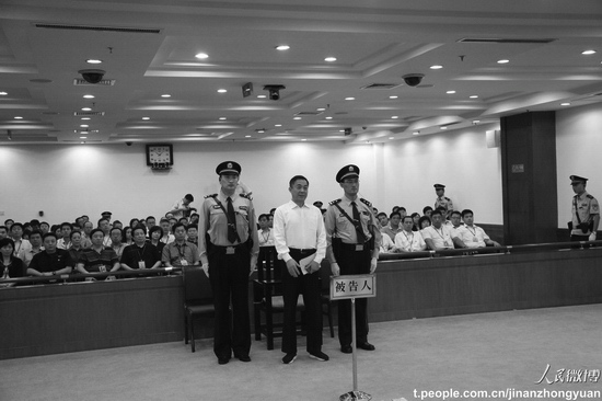 Bo Xilai stands between two officers at the court in Jinan, the capital of Shandong Province, on Sunday. He was sentenced to life in prison. (Weibo.com)