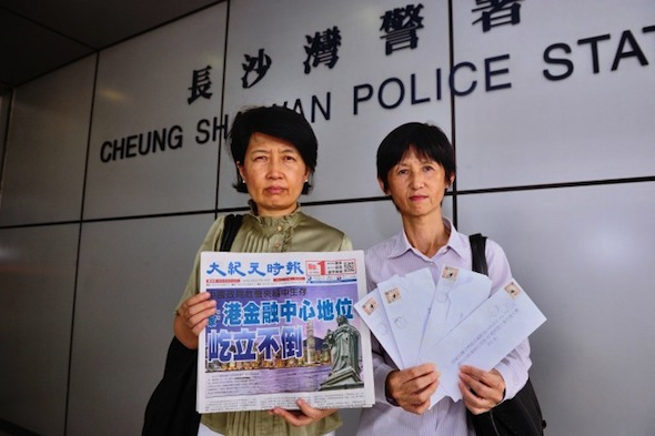 Two staff members of the Chinese-language edition of the Hong Kong Epoch Times stand outside the police station where they reported a campaign of harassment against the paper, on Sept. 12. The woman on the left holds a copy of the day's paper, and the woman on the right holds letters sent to advertisers that were meant to discredit the paper. (Song Xianglong/Epoch Times)