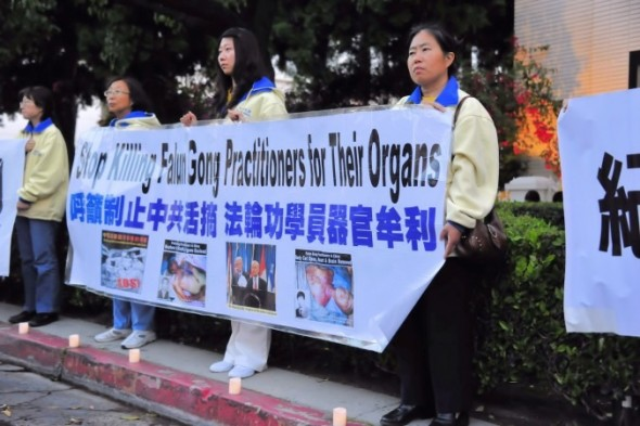 Falun Gong practitioners in the U.S. hold a banner with photos of fellow practitioners who were killed for their organs in China.