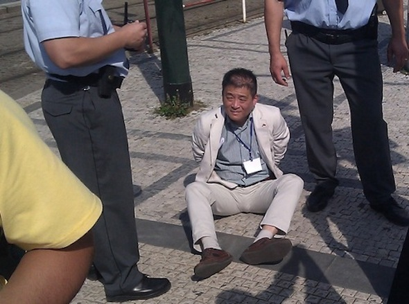 The Chinese official sitting on the ground, handcuffed by the Czech police. His name tag, reversed in the picture, indicates that he works at the Chinese embassy in Prague.