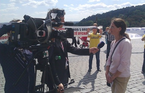 A reporter from Czech Television interviews a Falun Gong practitioner.