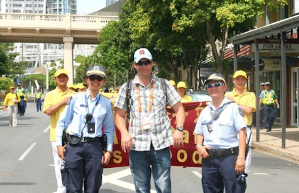 """Police officers get their photo taken before a banner that reads: """"Falun Dafa is Good"""""""
