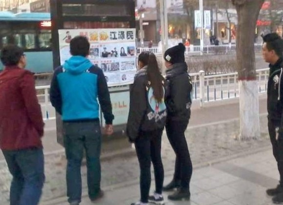 People read a poster with firsthand accounts from Falun Gong practitioners.