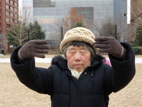 Ms. Tian practices one of the Falun Gong exercises outside the building that houses the Liberty Bell in Philadelphia on Feb. 13, 2015. (Friends of Falun Gong)
