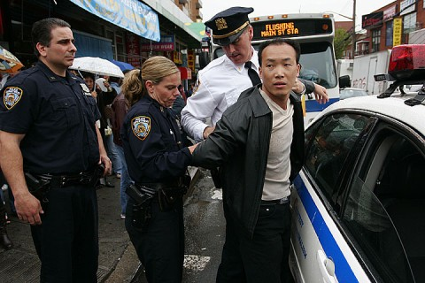 A pro CCP member is arrested by the police after assaulting a Falun Gong practitioner in Flushing, New York, on May 30, 2008. (Epoch Times)