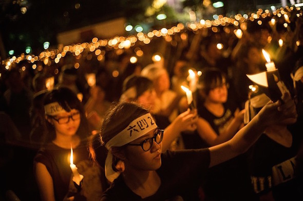 People take part in a candlelight vigil on the 25th anniversary of the Tiananmen Square protests during heavy rain on June 4, 2014 in Hong Kong. (Lam Yik Fei/Getty Images)