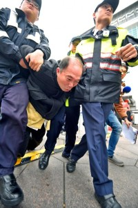 A pro-unification activist is taken away by Xinyi District police after allegedly insulting police as they were maintaining order in the area in front of Taipei 101. Mar 08, 2015. Photo: Wang Min-wei, Taipei Times
