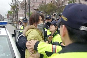 Police officers arrest a protesting member of pro-unification Concentric Patriotic Association of the R.O.C., yesterday. Taipei's newly appointed Xinyi District police precinct chief Wu Jing-tian made a striking first impression on citizens yesterday by ordering the arrest of several members of the infamous organization during his first official command.(CNA)