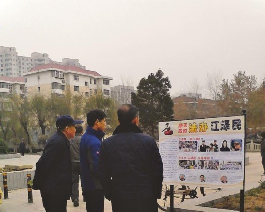 Passersby look at a poster in Shijiazhuang City, Hebei Province.