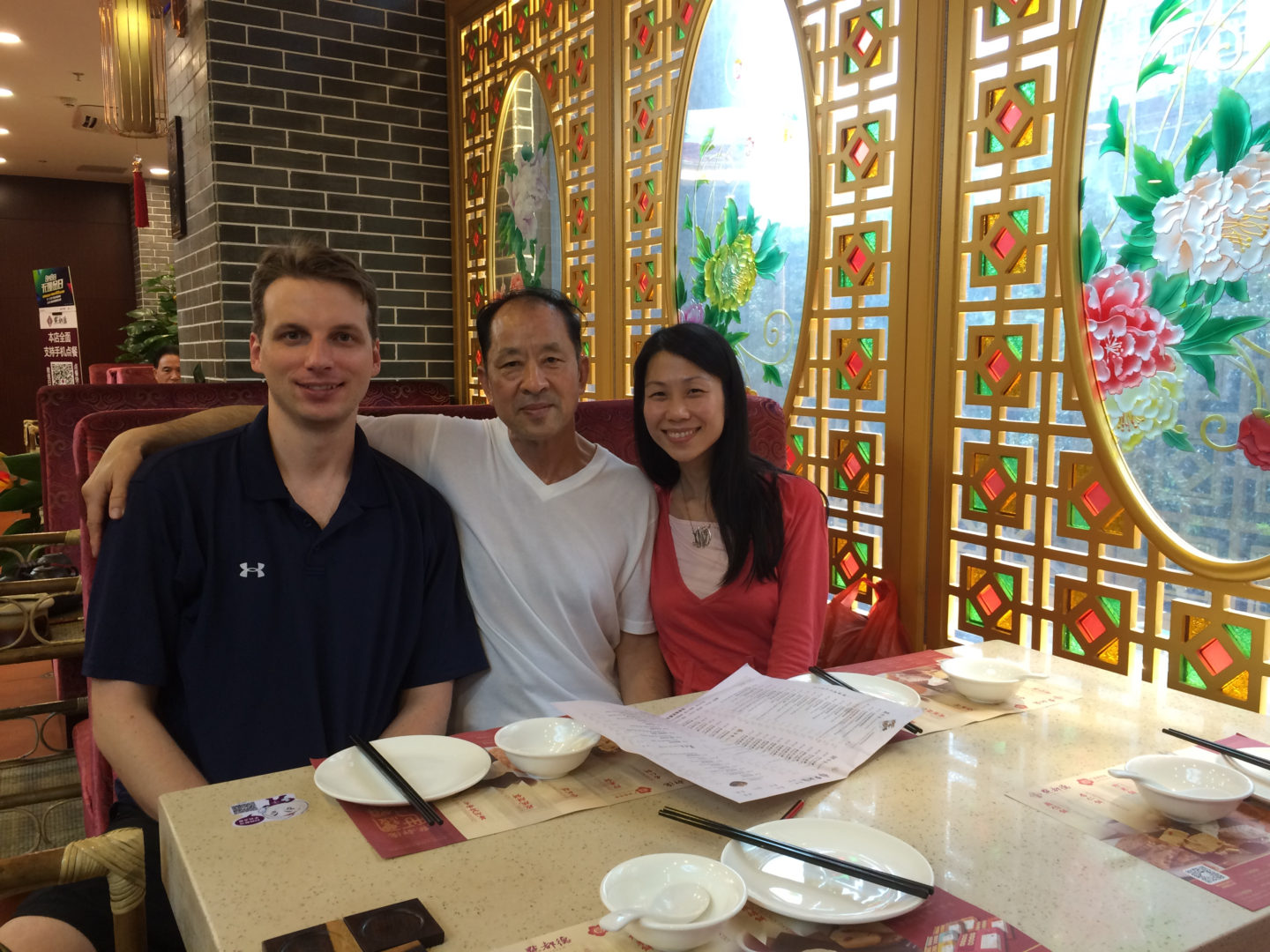 Danielle Wang (R) with her father, Wang Zhiwen (C), and her husband at a restaurant in China, summer of 2016. (Courtesy of Danielle Wang)