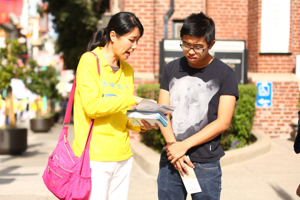 A woman from New York speaks to passerby about the persecution of Falun Gong in San Francisco on Oct. 22, 2016. (Benjamin Chasteen/Epoch Times)